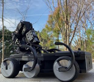 Робот с рукой прикрепил ноги к колесам и прошелся по камням